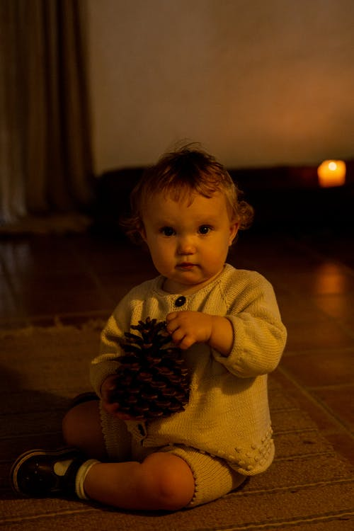 Cute little child sitting on floor with pine cone