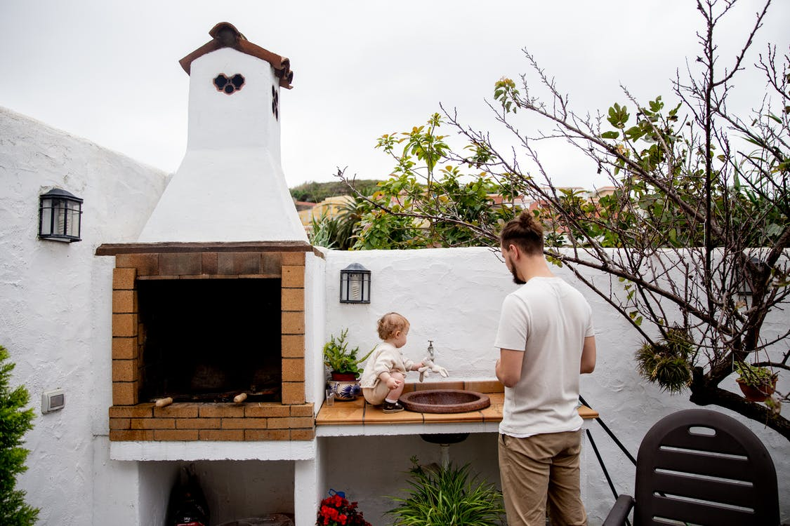 Man wearing casual clothes exploring outdoor kitchen with fireplace and sink together with cute toddler kid in backyard near white stone fence during daytime at countryside