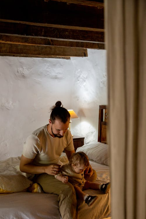 Focused bearded man with toddler kid sitting on bed in rural interior house