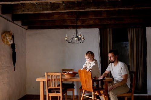 Cheerful cute little daughter spending time together with bearded father in casual wear inside aged room near wooden dinner table with wooden chairs at daytime