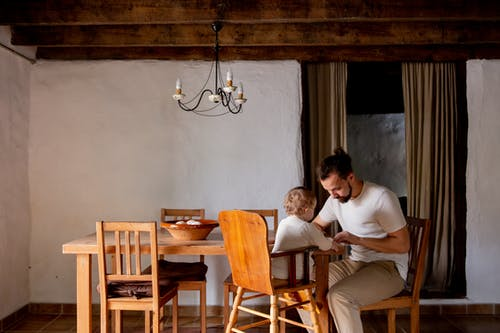 Focused young man with toddler girl sitting at desk in rural interior house
