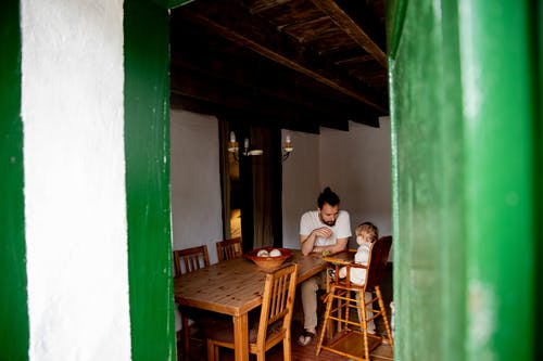 Young father with toddler child sitting at dinner table in rural interior house