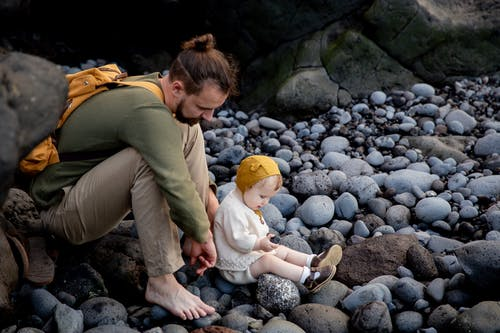 Man in Green Long Sleeve Shirt With His Baby in White Onesie Sitting On Rocks