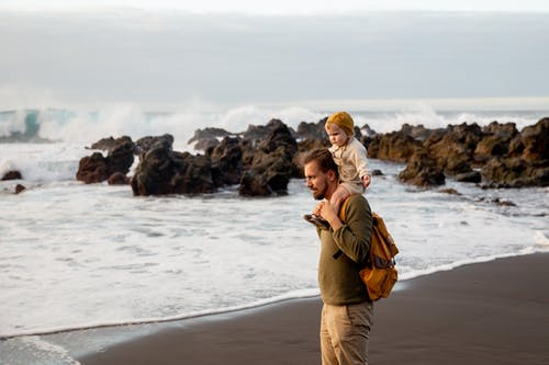 Father And Child Standing on Seashore