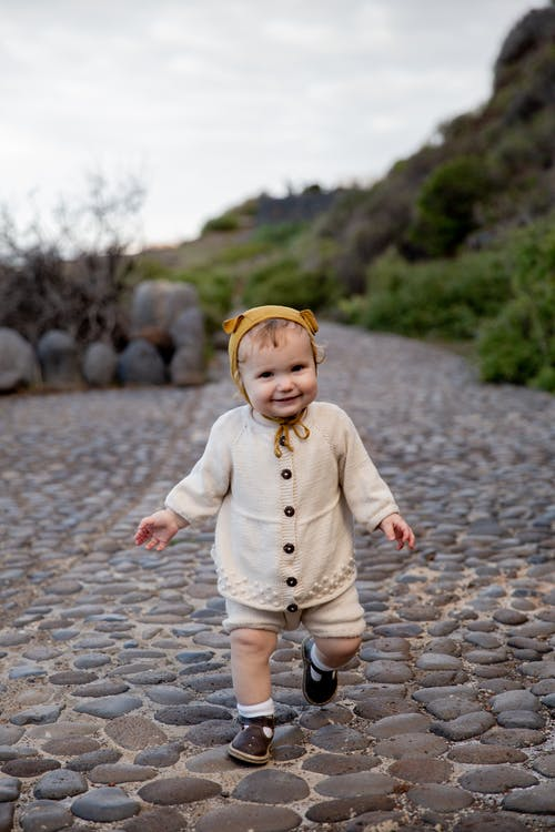 Adorable toddler child dressed in casual clothes and funny cap strolling on cobblestone pathway in countryside and smiling happily looking at camera