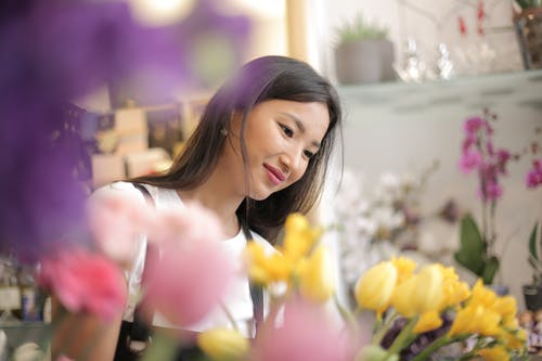 Satisfied smiling Asian female florist wearing apron surrounded by fresh colorful flowers and home plants during work in flower shop waiting for clients while looking down