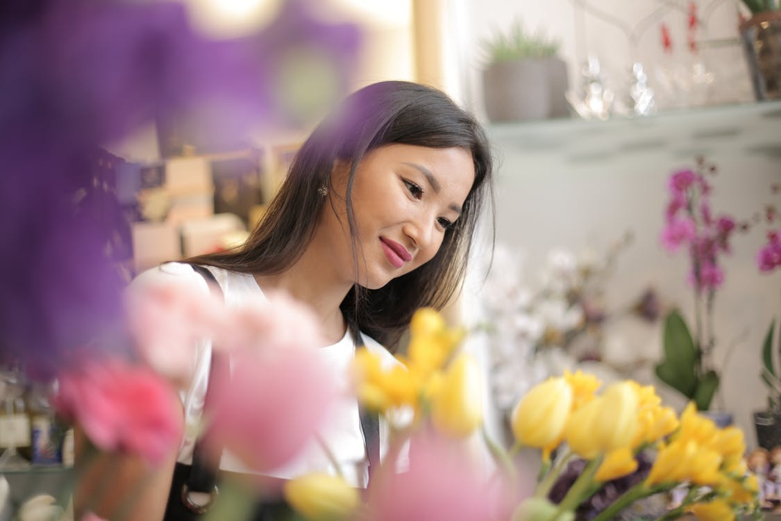Happy young ethnic businesswoman at own floral store