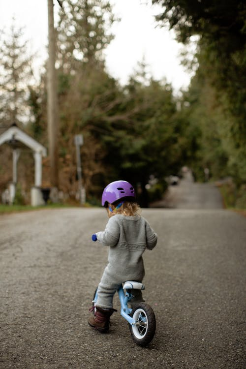 Back view of cute toddler child wearing helmet and warm bodysuit playing with bicycle on path near green trees on rural street