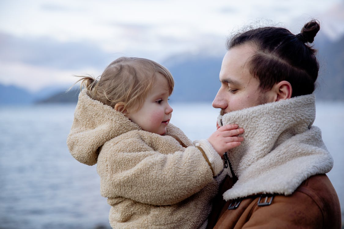 Satisfied young father and little daughter near sea in cold season