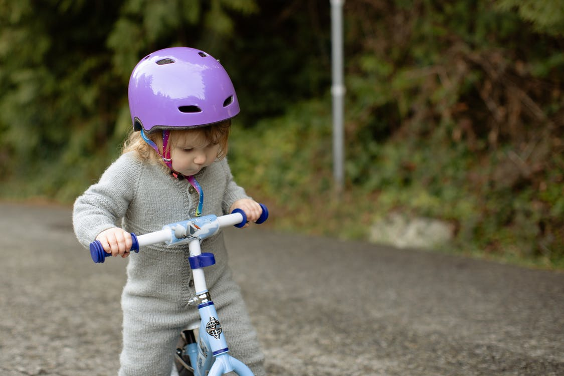 Cute toddler child wearing protective helmet and warm bodysuit playing with bicycle on road near green plants on rural street