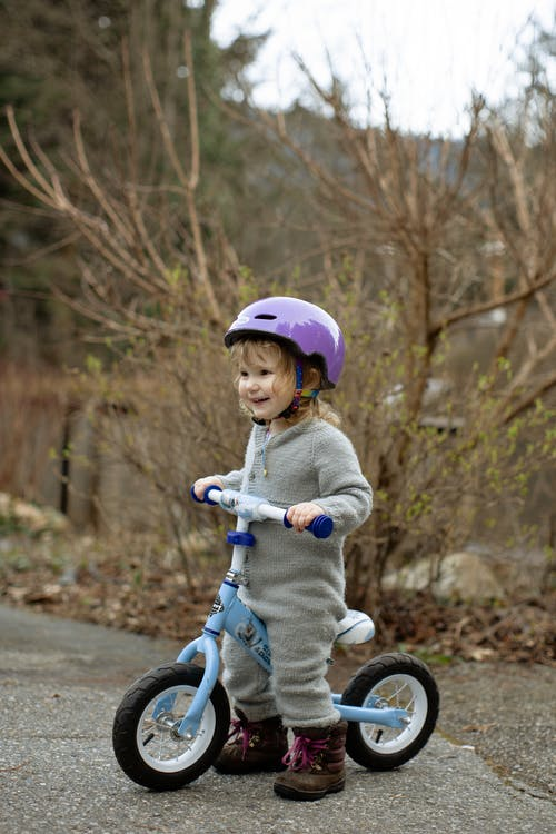 Cute little girl in helmet standing on balance bike on street