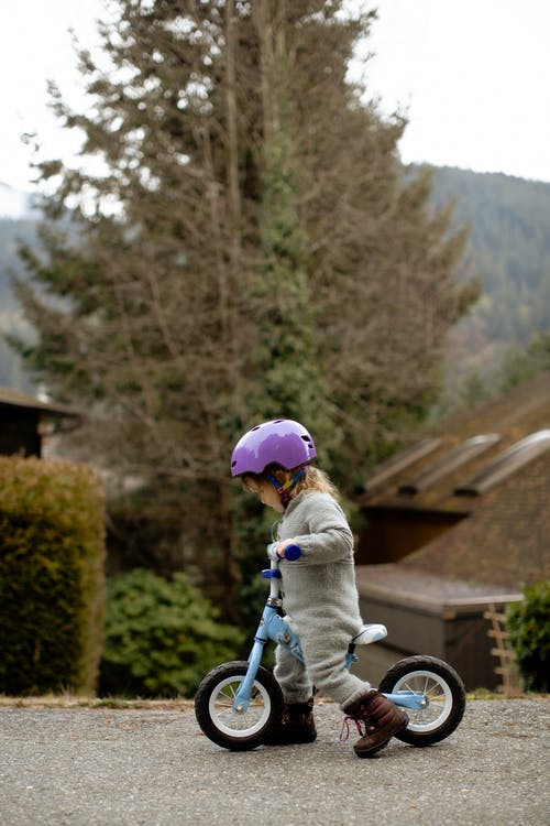 Side view of cute little girl in protective helmet and warm clothes riding balance bike along asphalt path on autumn street in countryside