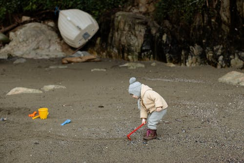 Little kid in warm clothes playing with toy shovel on sandy beach
