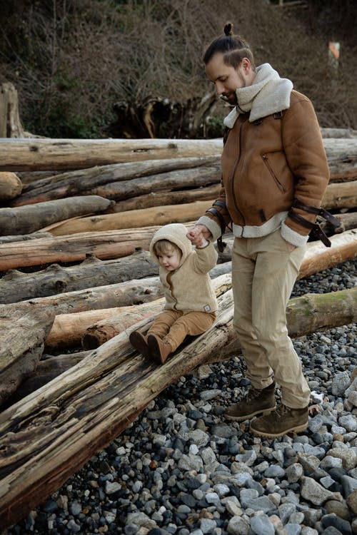 Positive father in warm outwear holding hand of little daughter while walking along rocky seashore and playing on log in autumn