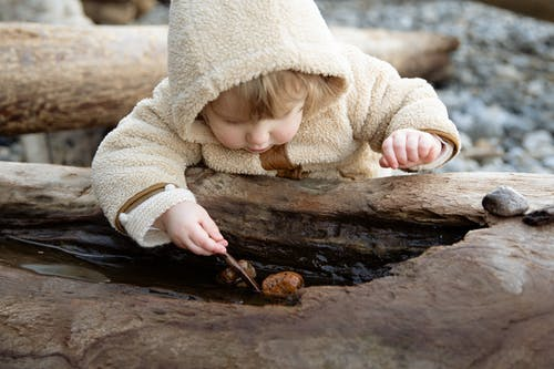 Cute little girl in warm coat playing with small pebbles on wet log while resting on shore in autumn day