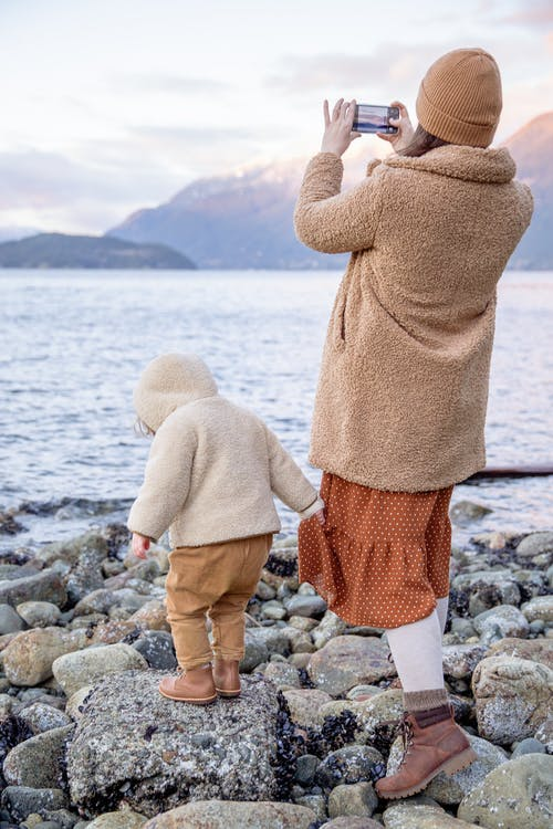 Mother and child in warm clothes standing on rocky seashore near water and taking photo on smartphone
