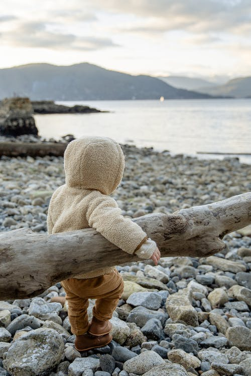 Side view of unrecognizable little kid in warm coat leaning on log and admiring calm water while standing on stony coast in overcast day in autumn