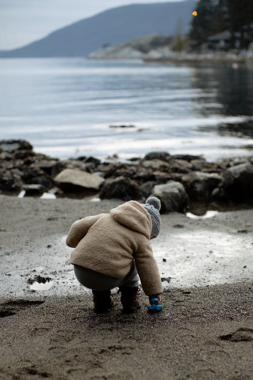 Little kid playing with toy on wet shore in overcast day during weekend