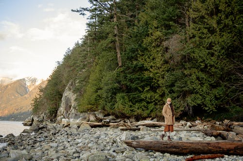 Young female traveler in warm outwear walking on log on stony coast near forest during weekend in autumn and looking away