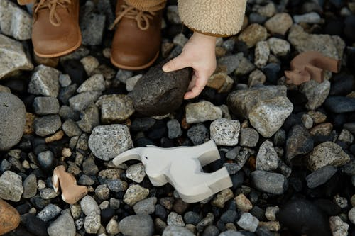 Unrecognizable crop kid playing with toys and stones on rocky ground