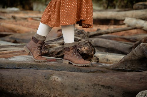 Unrecognizable crop woman wearing warm casual boots and skirt walking on log while spending time in countryside during weekend trip in autumn