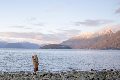 Mother with kid on hands standing on rocky coast near water and admiring view of mountains