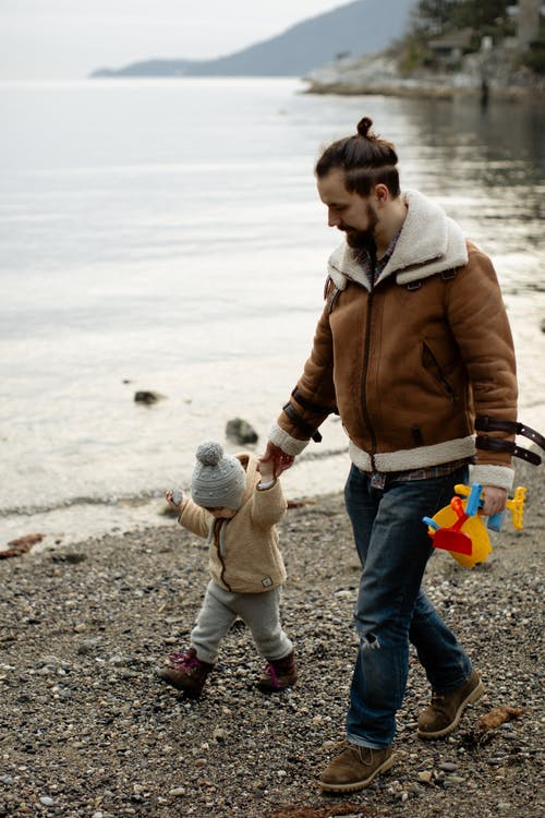 Father carrying toys while walking with little kid on beach near water