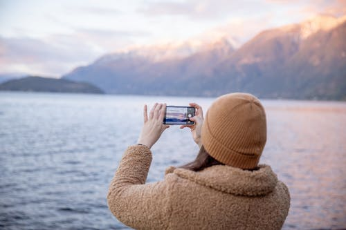 Anonymous female traveler taking photo on smartphone while standing on coast and enjoying seascape