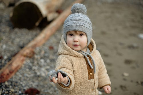 Child In Brown Coat And Gray Knit Cap Holding Rocks