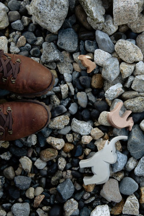 Anonymous crop child in warm boots standing on stony shore with toys