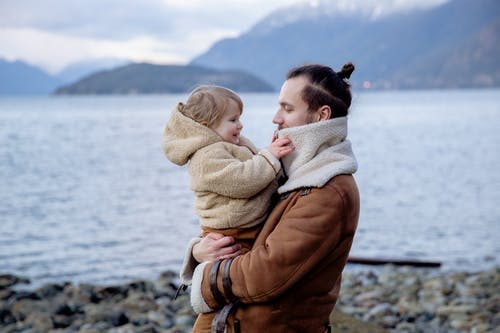 Side view of happy father and little kid in warm outwear on hands standing on stony coast near water and looking at each other during vacation