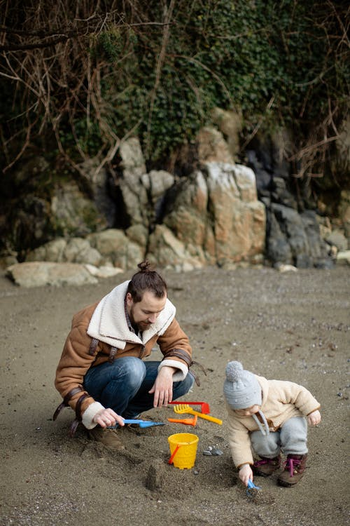 Father and little kid playing with toys in sand on shore