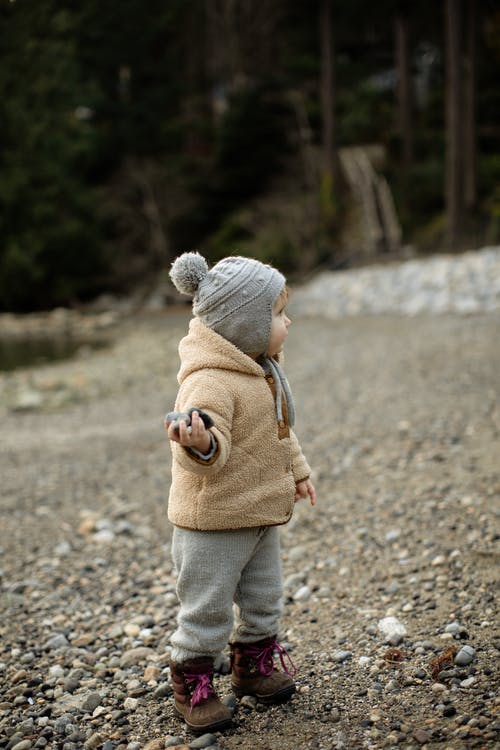 Cute little kid standing on stony ground with pebbles in hand