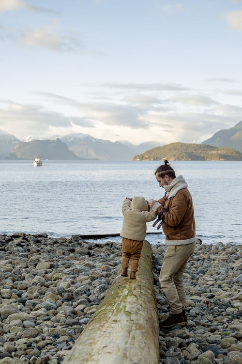 Bearded father in casual warm clothes helping little kid to balance on big log on stony coast near calm water during weekend in autumn