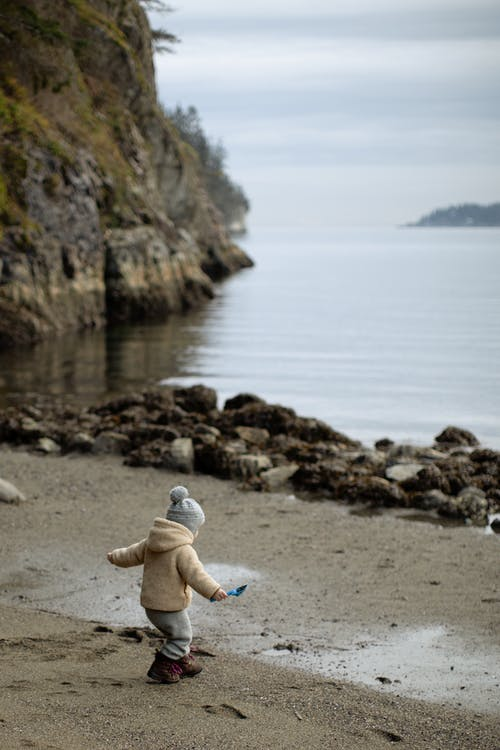 Unrecognizable little child playing on sandy shore near mountain