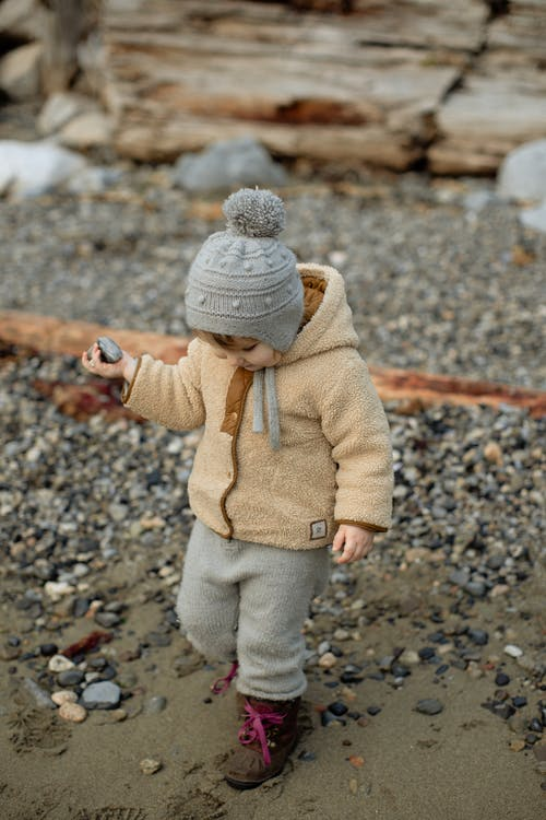 Curious little girl in warm clothing walking on winter beach