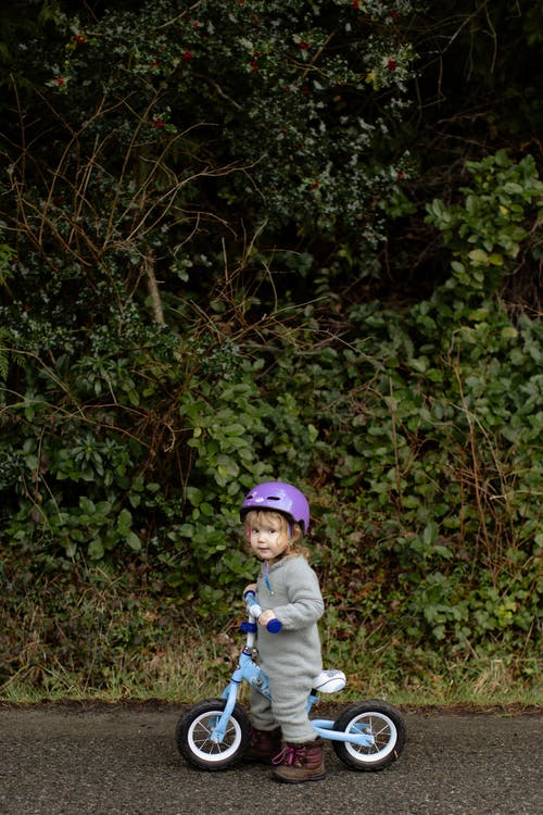 Adorable little girl riding bicycle on sidewalk against thickets of forest