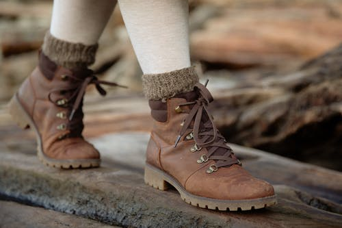 From above female feet in light tights and casual warm autumn boots standing on wooden log against shabby wooden planks