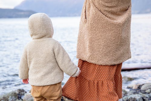 Anonymous baby holding skirt of crop woman near river in winter countryside
