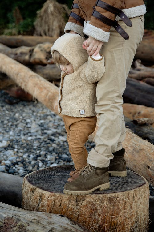 Crop person standing adorable kid on wooden logs in seashore