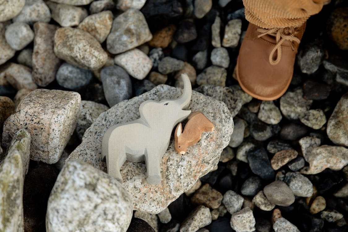 Faceless child playing with animal toys on rocky coast