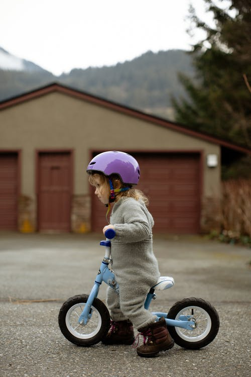 Cute child riding balance bike on street in countryside