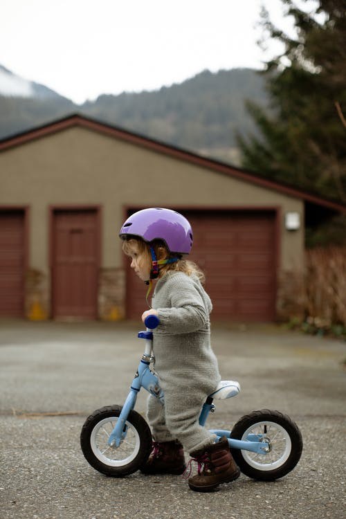 Side view of adorable little girl in protective helmet and casual warm clothes riding balance bicycle against garage building down street