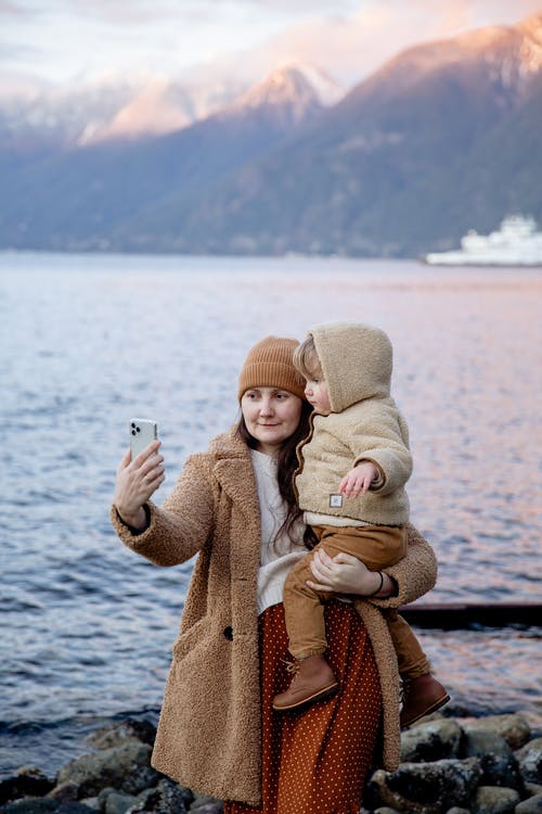 Calm woman carrying adorable child on hands and taking selfie on smartphone near river and mountains