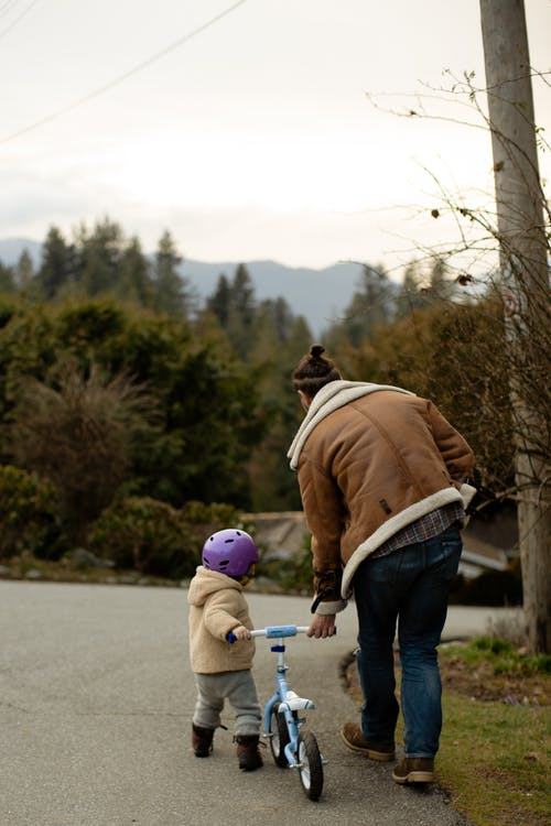 Back view of unrecognizable man and toddler wearing warm wear and walking on street with balance bicycle near green trees in countryside