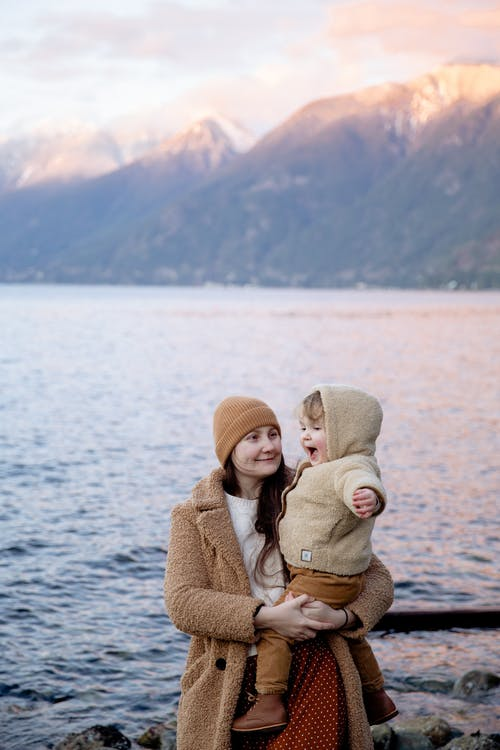 Positive mother holding cute baby during vacation near seashore in winter