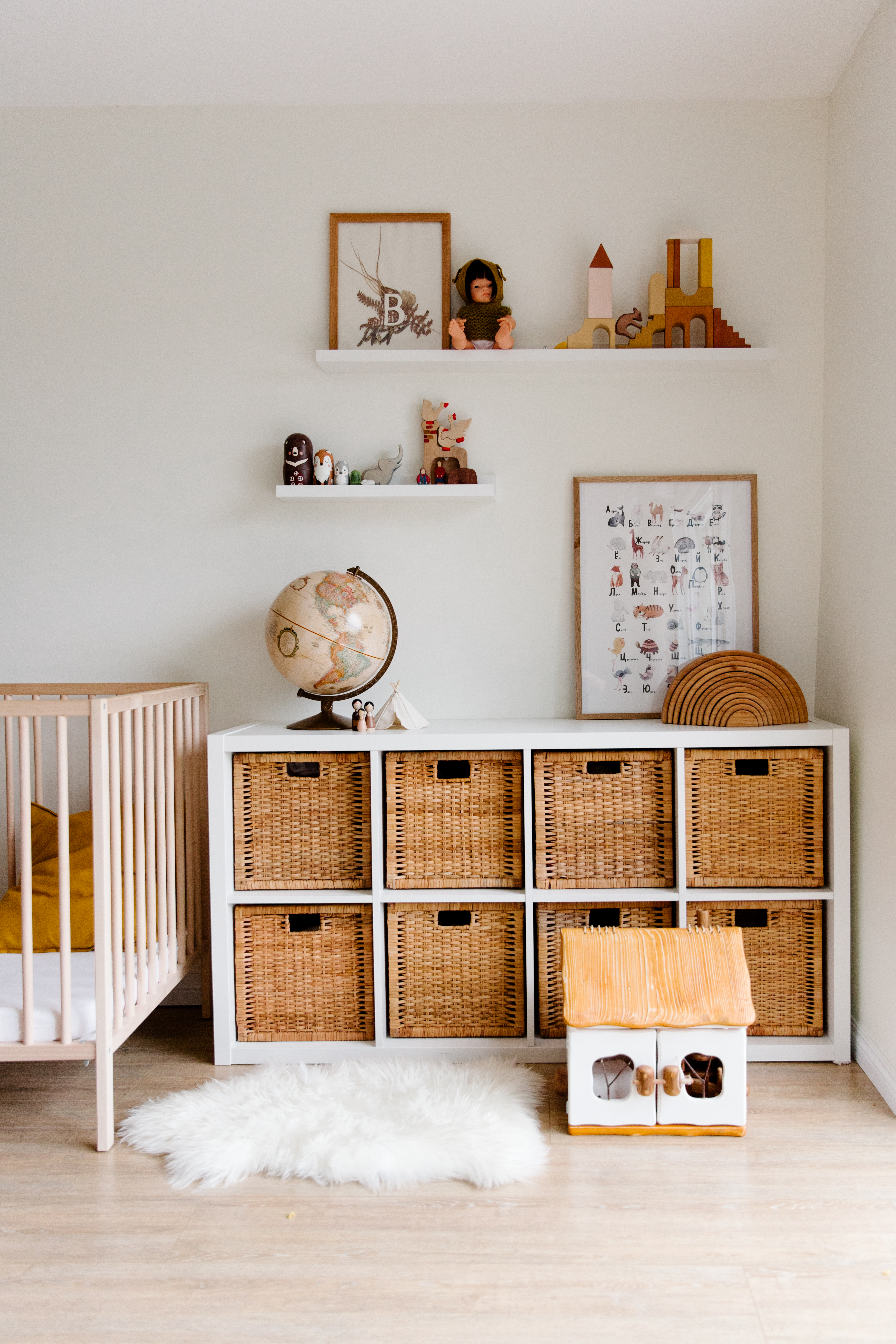 interior of children bedroom with wooden furniture and toys and globe placed on shelves in room