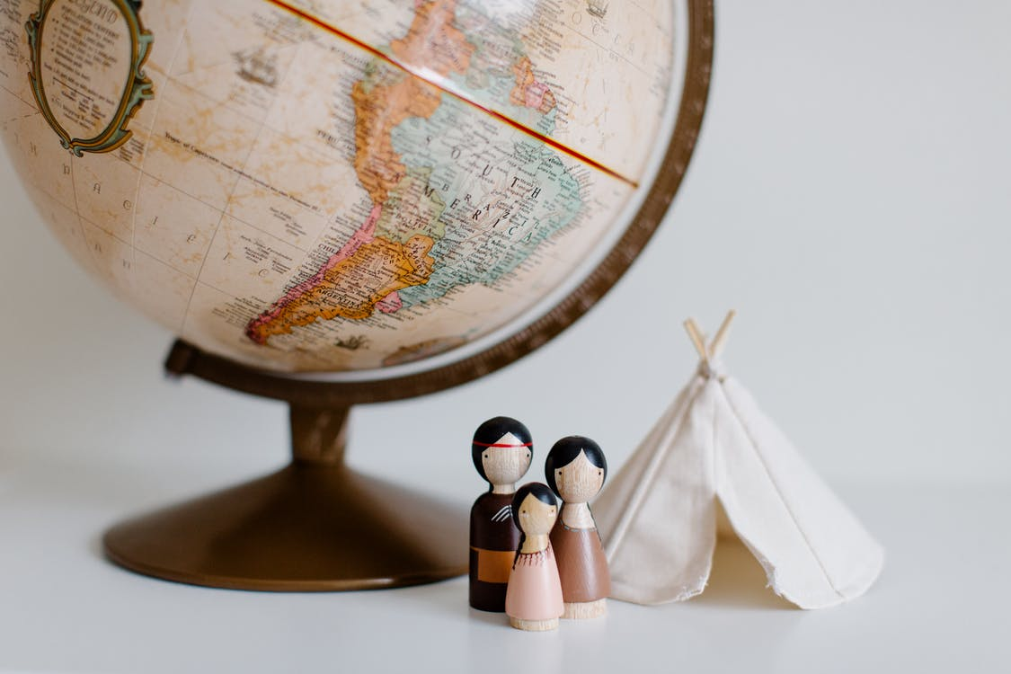 From above of miniature toys tipi house and American Indian family placed near vintage globe against gray background at daytime