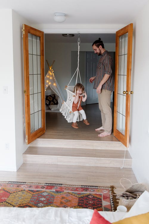Casual father helping daughter with swing at home