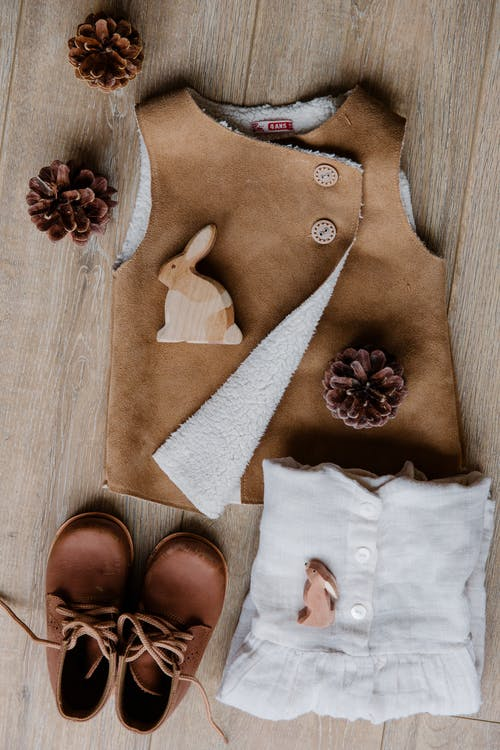 Top view of children boots leather brown vest and linen wear placed on floor decorated with cones and wooden rabbits